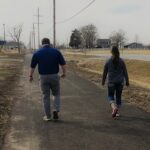 Two people walk along the newly constructed US 56 trail between the gas station and Dollar General in Edgerton