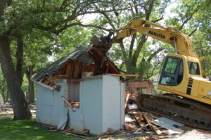 "A bulldozer knocks down the former ""cop shop"" near the library in downtown Edgerton"