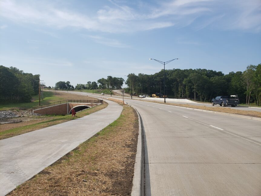 The image shows the new trail, four-lane concrete road and streetlights over Bull Creek