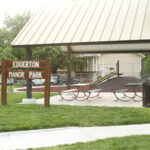 A wooden sign with the words Edgerton Manor Park in white lettering sits in front of a pavilion with a cream-colored roof and picnic tables. Playground equipment is seen in the background, including a slide and a jungle gym.