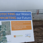 A sign reads protecting our waters, supporting our future during the grand opening of the Big Bull Creek Wastewater Treatment Plant
